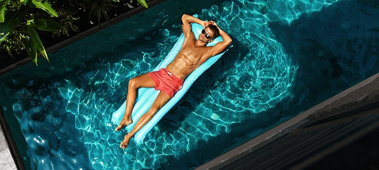 Mann entspannt sich im Swimming Pool